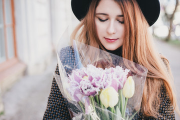 Young beautiful fashion woman wearing hat walking on a city streets with flowers in her bag