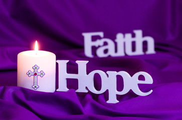 Candle burning  with words Hope and Faith on purple fabric background