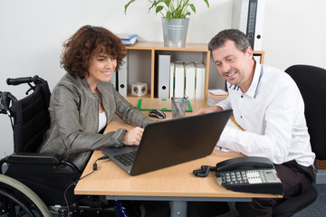 Confident disabled business woman in wheelchair working at office desk