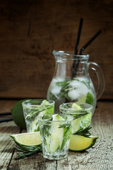 Refreshing drink with rosemary, lime and honey on the old wooden