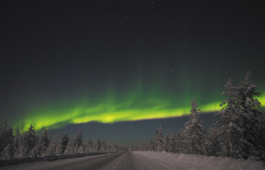 Winter night landscape with road and green polar light over the forest