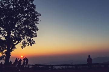 Peoples and trees silhouetted with stunning sunset