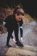 Fit brunette with armband tying her shoe lace