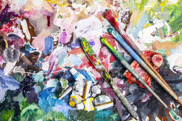 Palette of artist for mixing paints and a brush with a knife