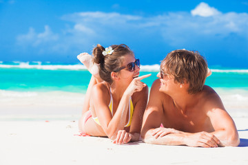 happy romantic young couple lying at a tropical beach