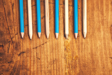 Blue and brown lined up pencils on rustic wooden table