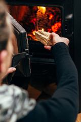 Woman Putting Logs In Fireplace