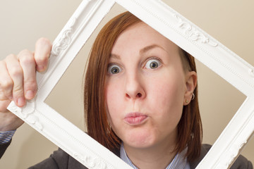 Beautiful woman with red hair looking through a white picture frame.