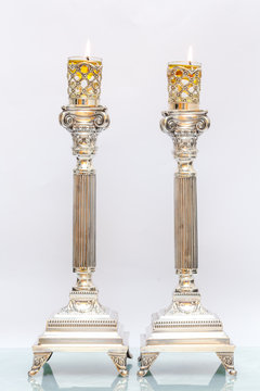 Shabbat candles. Silver candlesticks with olive oil. Light background