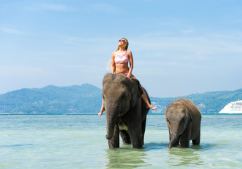 Woman on the elephant  and baby elephant in water. Thailand vacation.