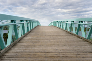 Wooden Footbridge with Metal Railings on a Cloudy Day