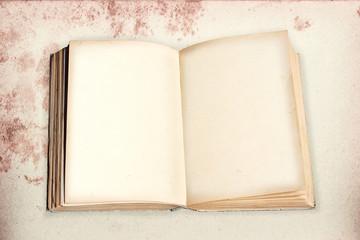altes Buch mit leeren Seiten auf fleckigem Hintergrund. Retro De