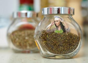 Conceptual shot of a woman cook inside a jar of condiments