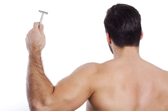 Closeup of muscular man holding razor, back turned, man shaving concept