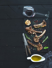 Grilled lamb chops. Rack of Lamb with garlic, rosemary, spices on slate tray, wine glass, oil in a saucer over black wood background