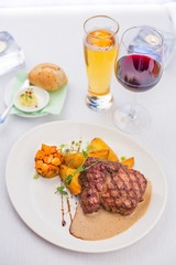 Delicious grilled beef steak with colorful vegetable garnish on a white plate, well served lunch/dinner table