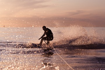 Wakeboard ride on tranquil waters at a sunset Wall mural