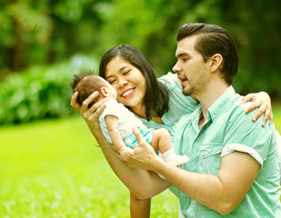 Happy Mixed Race Family Playing with New Born Baby at Park
