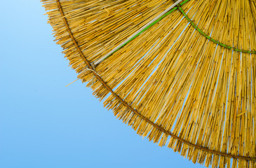 detail of a hay parasol with a blue sky on the background.