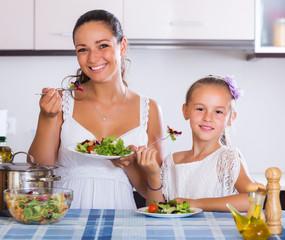 Woman and girl holding salad