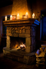 Fireplace room. Chimney, candles and woodpile. Chimney place.