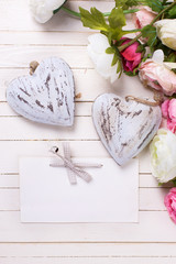 Flowers with  two decorative hearts  and empty tag on white wood