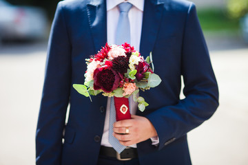 Elegant handsome groom in blue suit with wedding bouquet