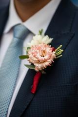 Elegant stylish groom in black suit with fresh flower boutonnier