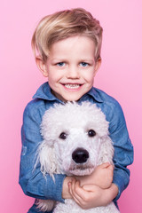 Beautiful boy with Royal Standard Poodle. Studio portrait over pink background. Concept: friendship between boy and his dog