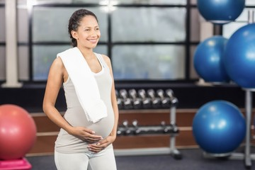 Smiling pregnant woman with towel on shoulder