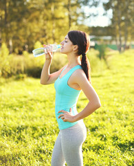 Sport and fitness concept - beautiful young woman drinking water