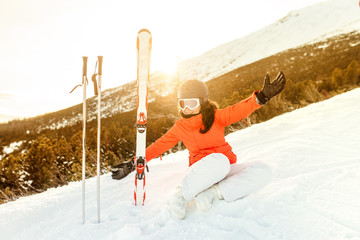 Smiling portrait of a young woman enjoying the mountains. Happy skier relaxing