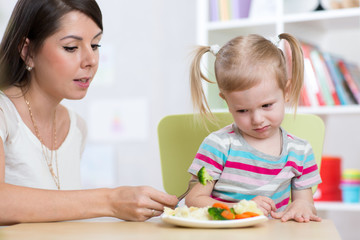 Child girl looks with disgust at healthy vegetables. Mother convinces her daughter to eat food.