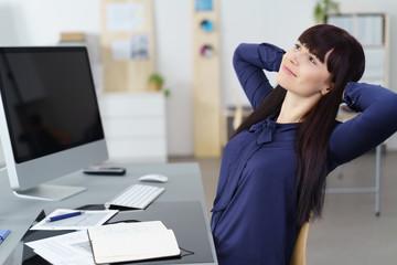 frau im büro lehnt sich zufrieden zurück