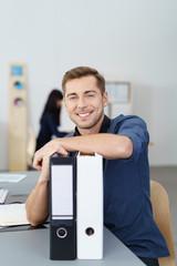 mitarbeiter im büro stützt sich auf aktenordner