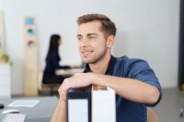 motivierter mitarbeiter im büro stützt sich auf aktenordner
