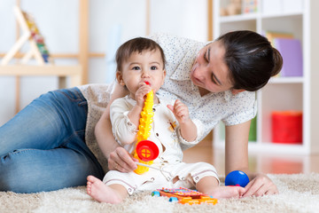 mom and baby playing musical toys at home