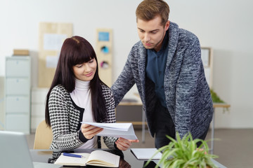 zwei mitarbeiter im büro schauen zusammen auf einen brief