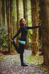 Fit brunette stretching against a tree
