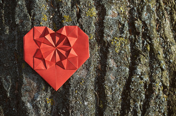 Red folded paper origami heart on rough wood bark. Valentines horizontal postcard template. Space for text, copy, lettering.