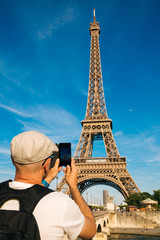 Tourist man taking pictures of the Eiffel Tower with a smart phone