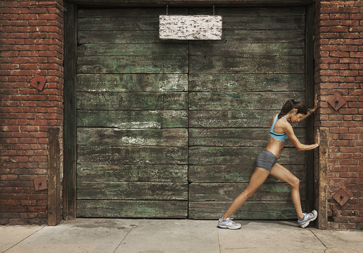 A woman in running gear, crop top and shorts, stretching her body and preparing for a run, or cooling down after exercise.
