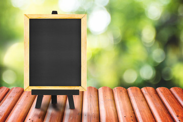Blackboard on Log wood tabletop with blurred green nature backgr