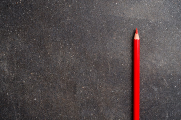 Red pencil on dark table