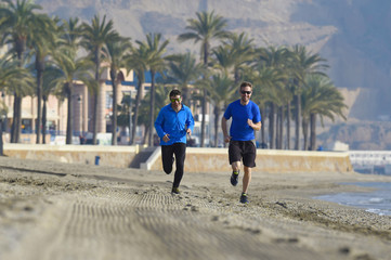 two men friends running together on beach sand with palm trees m