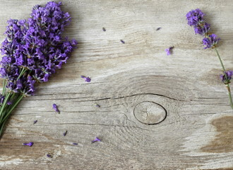 Fresh lavender flowers on a wooden background. Decorative border or frame with lavender and old wooden plank. Photo above.