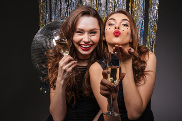 Cheerful beautiful young women having party and sending kiss
