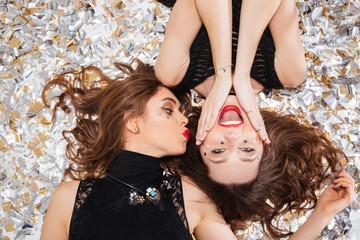 Two joyful women lying on white background with confetti