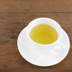 The cup of Japanese green tea on wooden planks.