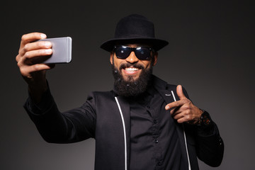 Afro american man in fashion cloth making selfie photo